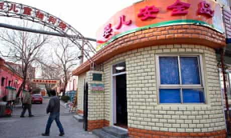 People walk past a  cream brick building named in Chinese 'baby safety island'