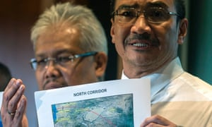 Malaysian acting transport minister Hishamuddin Hussin shows a map showing the possible flight path of the missing plane.