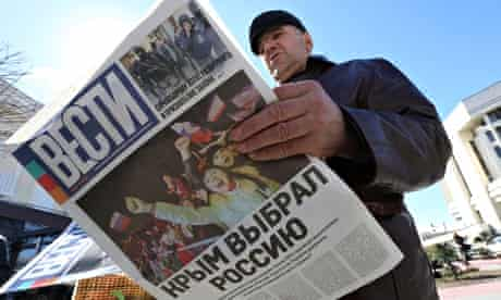 A man reads a newspaper with the headline 'Crimea chooses Russia' on a street in Simferopol