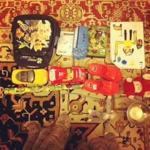 a ben 10 bag pencil case cars and sandals on a carpet