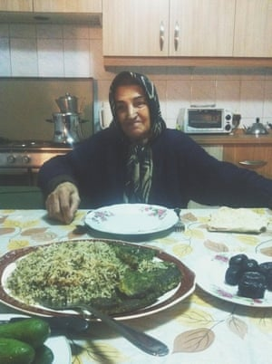 an iranian woman sitting at a kitchen table in front of a plate of koo koo sabzi