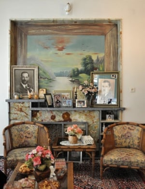 a landscape painting, framed photos and two wooden chairs in a living room