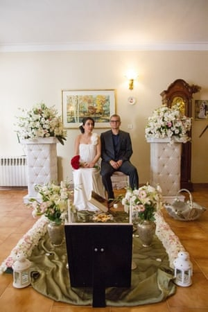 a bride and groom sitting amongst wedding decorations