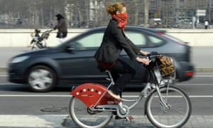 A woman rides a Velo'V, Lyon's bike share system, with a scarf covering her nose and mouth during an episode of heavy pollution in central Lyon