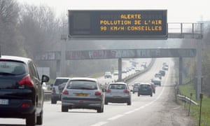 """Cars drive past a traffic board reading """"Warning air pollution 90 km /h recommended"""" near Rennes, western France"""