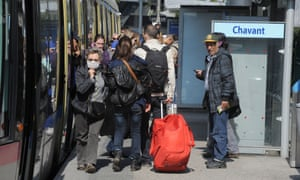 People stand in front of a tramway 2014 in the city of Grenoble