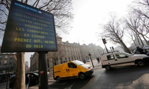 """A Paris city information board which reads, """"Pollution - Avoid taking your cars; prefer public transportations, take the bus  or your bicycle"""""""
