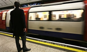 A man waits for a Northern Line underground train, tube, on a platform saying mind the gap