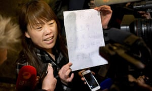 """A relative of a Chinese passenger aboard the missing Malaysia Airlines Flight MH370 shows a paper reading """"Hunger strike protest, Respect life, Return my relative, Don't want become victim of politics, Tell the truth""""."""