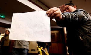 """A relative of a passenger onboard the missing Malaysia Airlines Flight MH370 shows a paper with a message from family members at a hotel in Beijing The message reads, """"Hunger strike. Tell us the truth. Return us our families""""."""