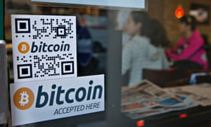 Signs on a window advertise a bitcoin ATM machine that has been installed in a Waves Coffee House in Vancouver, British Columbia.