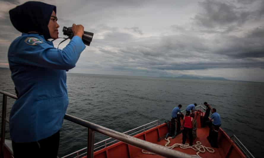 A member of the Indonesian search team uses binoculars to look for flight MH370 in the Andaman Sea, near the northern tip of Sumatra island.