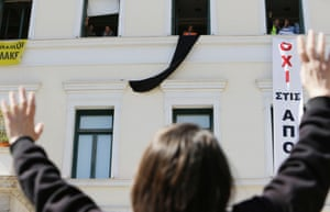 A protesting school guard waves to her colleagues as they dangle banners from the Athens City Hall, on Tuesday, March 18, 2014.