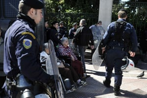 Patients of a care foundation for diasabled people sit on their wheelchair in front of police blocking their way to the Prime minister's office in Athens on March 18, 2014.  Patients and their families gathered  to protest against the cuts of state subsidies towards the care which leeds to its closure.