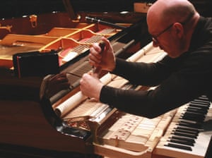 Technician Peter Salisbury works on the action of a Yamaha grand piano at the Queen Elizabeth Hall, London.