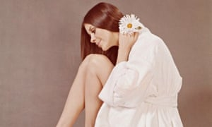A young woman in a towelling bathrobe with a daisy, circa 1970
