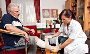 Nurse bandages an elderly man's leg