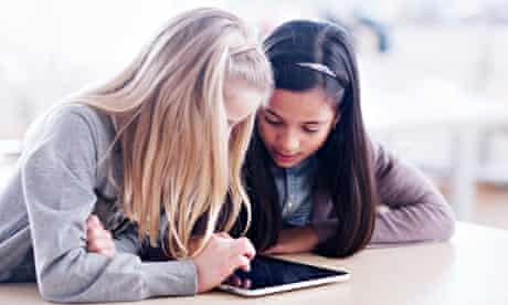 Two girls using tablet computer in school class