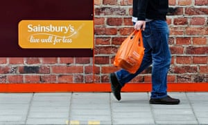 A shopper passes a sign for a Sainsbury's store