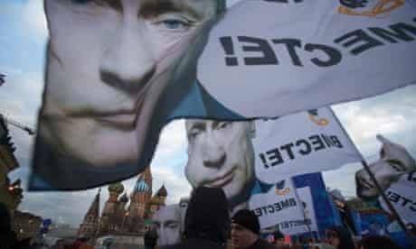 """People rally in Red Square with banners and portraits of Vladimir Putin, reading """"We are together."""