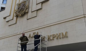 Workers dismantle the Ukrainian signs on Crimean Parliament building on March 18, 2014 in Simferopol, Ukraine.