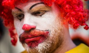 """A man named Ben, who chose not to give his last name, dressed as the McDonald's mascot Ronald McDonald, participates in a protest for higher wages for fast food workers in New York City. During the protest Ronald McDonald was """"arrested"""" by other protesters inside a McDonalds for corporate greed and withholding wages."""