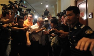 A Chinese relative of passengers from the missing Malaysia Airlines flight MH370 is stopped and escorted away by Malaysian police from entering the media centre before the start of a press conference at a hotel near Kuala Lumpur International Airport.