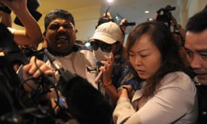 Rlatives of passengers from the missing Malaysia Airlines flight MH370 are stopped and escorted away by Malaysian police from entering the media centre before the start of a press conference at a hotel near Kuala Lumpur International Airport.