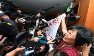 A Chinese relative of passengers aboard a missing Malaysia Airlines plane cries as she holds a banner in front of journalists reading 'We are against the Malaysian government for hiding the truth and delaying the rescue. Release our families unconditionally!""