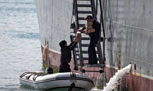 Ukrainian navy sailor in a dinghy passes bread to a sailor from command ship Slavutych at Sevastopol