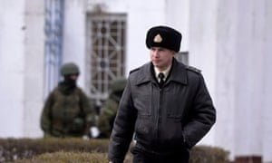 A Ukrainian officer leaves the Ukrainian navy south base after it was taken over by Russian forces