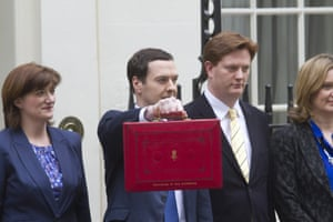 Chancellor George Osborne holds his budget box next to members of the Treasury