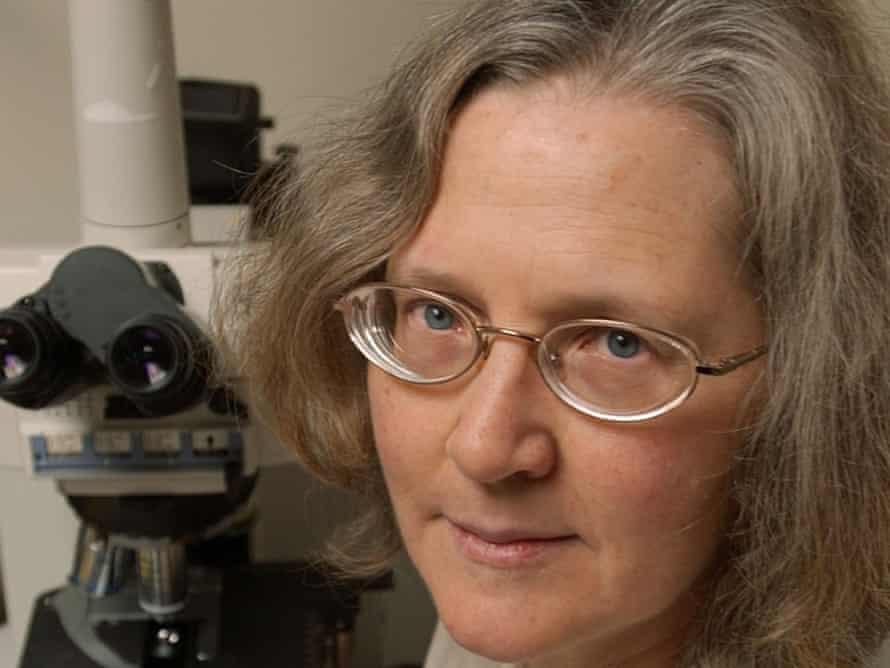 Photograph of Elizabeth Blackburn next to a microscope