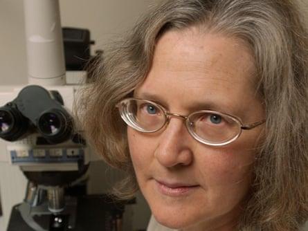 Photograph of Elizabeth Blackburn next to a microscope