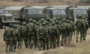 Soldiers who were among several hundred that took up positions around a Ukrainian military base walk towards their parked vehicles in Crimea on 2 March, 2014 in Perevanle, Ukraine.
