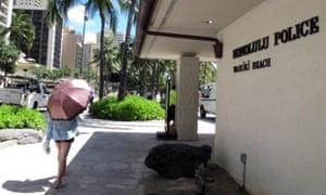 A pedestrian walks in front of a Honolulu Police Department station in Honolulu's tourist area of Waikiki