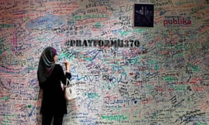 A woman writes on a message board in support of the passengers of the missing Malaysia Airlines Flight MH370, at a shopping mall near Kuala Lumpur.