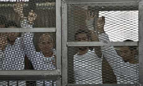 The four jailed al-Jazeera journalists in a cage during their trial in Cairo