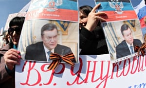 Pro-Russian protesters hold portraits of Yanukovych