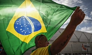 A man holds a Brazilian national flag outside Arena Amazônia, Manaus, where England will play Italy