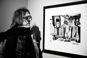 Mick Rock looking at his photograph of David Bowie and Mick Ronson from 1973