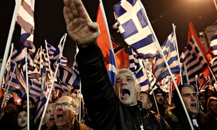 A middle-aged man raises his hand in a Nazi-style salute to a backdrop of Greek flags
