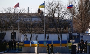 From left: flags of the Ukrainian marines, Ukrainian national flag and the Russian national flag wave at the the Ukrainian marine base in the city of Feodosia, Crimea. The Russian defence ministry said the Russian flag was now flying over 189 military facilities in Crimea.