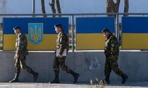 Russian officers walk past the Ukrainian marine battalion headquarters in the Crimean city of Feodosia.