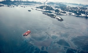 Staining the vista of the Chugach Mountains, the   Exxon Valdez lies atop Bligh Reef two days after the grounding