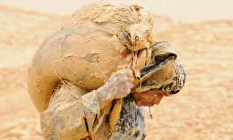 A man caked in wet mud struggles under a heavy load at a rare earth metals mine at Nancheng, China