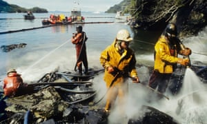 Original caption: Workers spray hot water on oil-covered beaches in Prince William Sound, Alaska. Exxon Valdez oil spill, USA, 1989