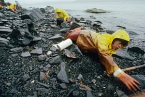 A volunteer uses paper towels and spoons to wipe oil off her beach at Larsen Bay, Kodiak Island. Exxon Valdez oil spill, Alaska,