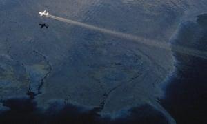 A modified C130 plane sprays dispersant on the Exxon Valdez oil spill. Alaska, USA, 1989 -
