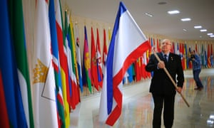 Russian lawmaker Alexander Chekalin adds a Crimea flag to a line of Russian regional flags in the Russian Federation Council building in Moscow, marking the region's accession to Russia.